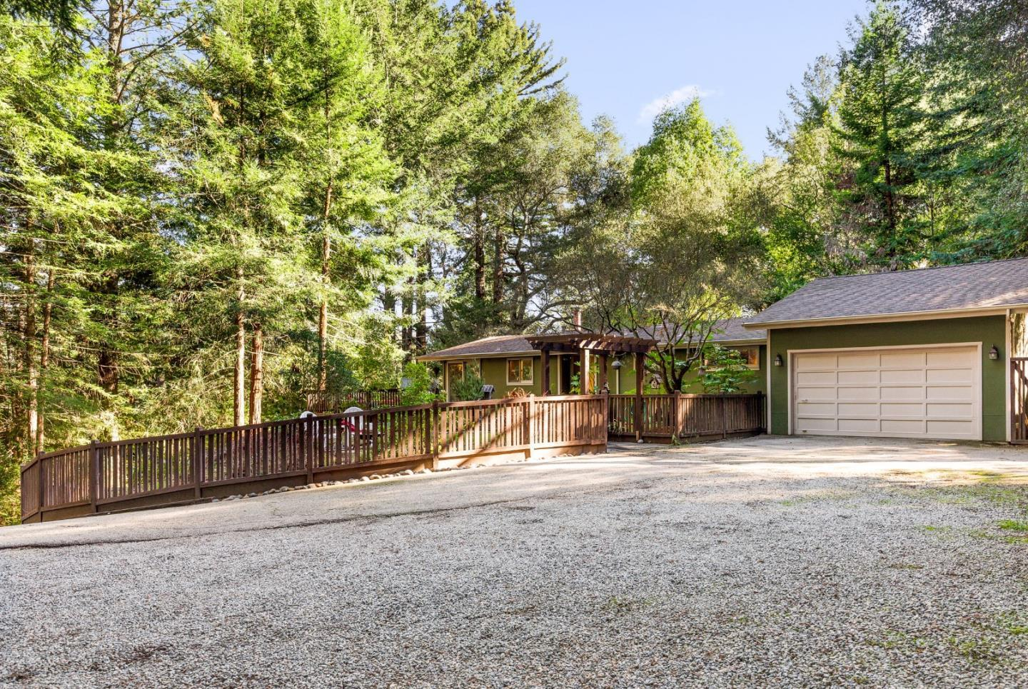 This single-level home nestled in a sunny clearing and surrounded by nearly an acre of forest views with plenty of outdoor space for relaxing and gardening make this spot a private and peaceful haven from the hustle & bustle of modern life, yet so close to everything you need. One of the most private and peaceful properties in the area. The flat lower parcel boasts a large cleared site suitable for a pool, garden, camping, tennis court, or even an ADU. The 2BR/2BA + Office/Den home is well designed with quality, function and style in mind including solid cherry hardwood floors, open-beam vaulted ceilings, and a wraparound deck. At the end of the hallway, you'll find a bonus room with loft suitable to be made into a 3rd BR that integrates perfectly into the home's style and floor plan. Artist Studio / Workshop with electricity hooked up and water available nearby. Local estimate to repair driveway: removal of 5 roots, widen entry for trailer/boat towing, slurry 3,300 SF is about $6,000.