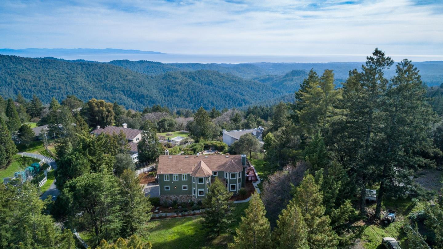 Spellbinding views over ridges and canyons to the Monterey Bay! Beautifully maintained & updated, enjoying a peaceful setting on private dead end road, only minutes from local amenities inc. Summit store, schools, churches & wineries. Enjoy hiking trails in the redwood forest, just a short stroll down the quiet country lane. The 2 story home comprises a formal living room & sep. family room, formal dining & bright open kitchen with breakfast dining. 4 bedrooms + workout room/den or 5th bed (no closet). 3 master suites inc. one on 1st floor, ideal au pair or in-law quarters. Layout offers potential for self contained apartment. 4 full baths (3 with new quartz vanity tops) & 1/2 bath. Swimming pool & spa with expansive patio decking, full sun all day! Ideal conditions for solar. Gravel paths lead to raised gardens, low maintenance landscaping, grassy front yard...over an acre all usable and perimeter fenced. 20-25 mins to Los Gatos or Santa Cruz. Excellent shared well, Comcast Internet!