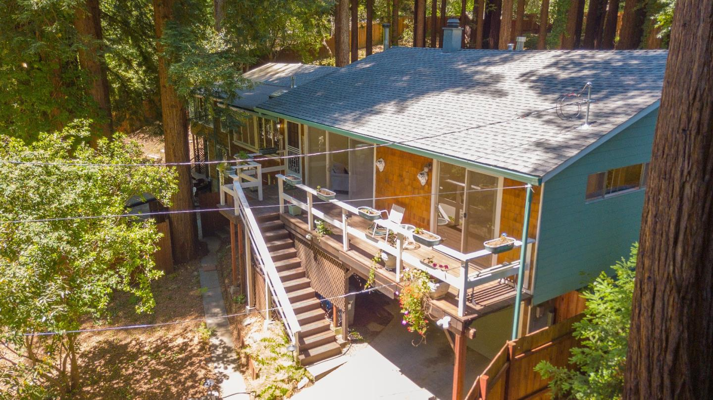 "EXTRA, EXTRA, READ ALL ABOUT IT! Half acre+ fenced lot less than 2 miles from town. Wonderful mix of sun with shade from majestic redwoods. Original 1940 construction maintains some of its rustic charm. Now with permitted 5 bedrooms, 2 baths and large family room you'll find plenty of space to roam.Cozy wood burning fireplace in the family room and a woodburning stove in the living room can warm the cool nights or chilly winter days. Sweet sunroom off the kitchen opens out to a sunny deck to enjoy the natural wonders around you. Walk-out basement is partially finished and could be add'l unit, also laundry room, and storage room are all Extra and not counted in square footage. A chair lift can carry elders or groceries from basement to main level. A valuable Generac generator will complete your sense of comfort and well being. Develop your visions and dreams in this ""paradise"" in the mountains. Seller prefers ""As Is""."