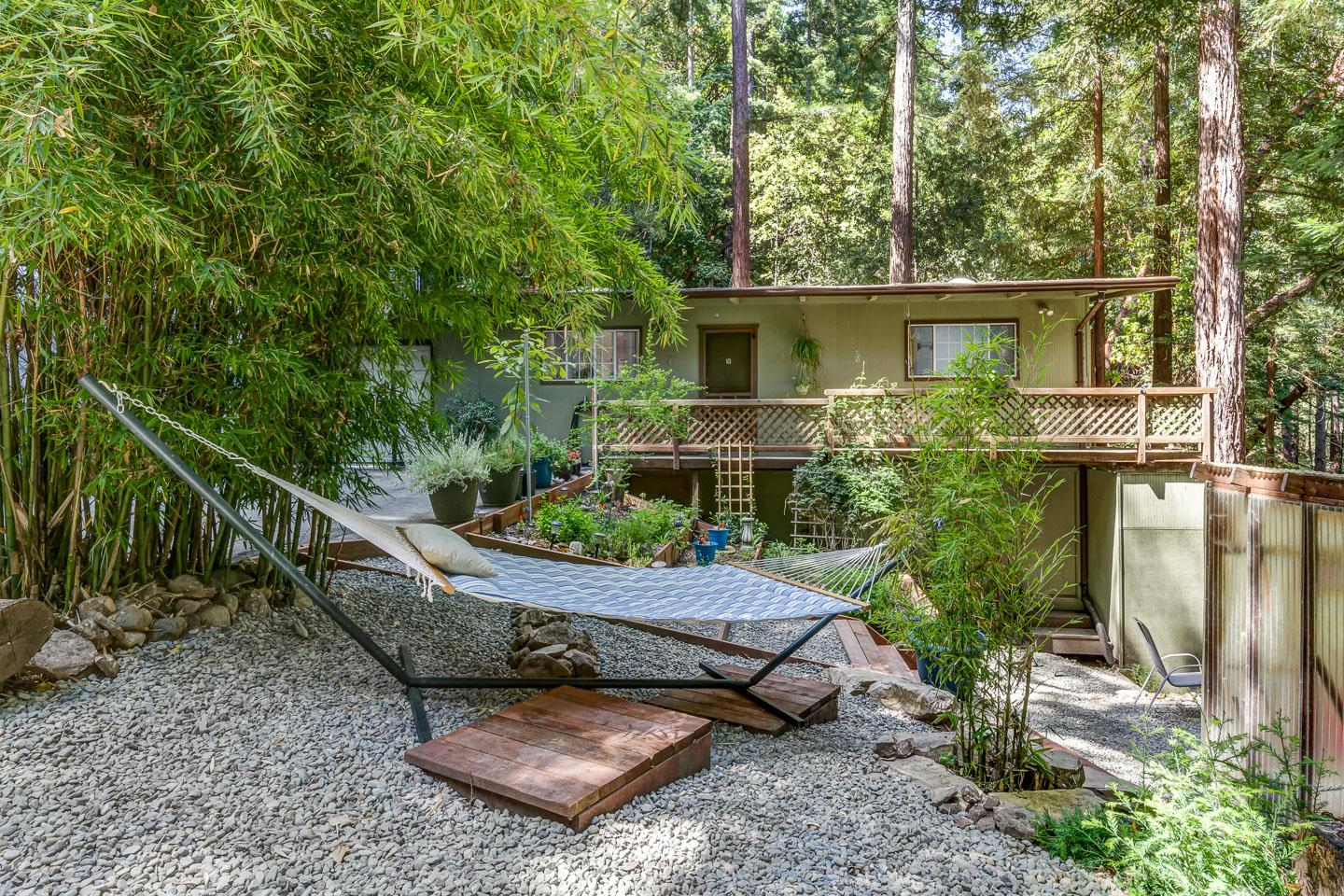 Surrounded by beautiful redwood trees is this charming, single-level home consisting of two parcels. Property includes a beautifully maintained garden with sunshine, a fun tree house, and a patio and deck perfect for relaxing or entertaining. Plus an amazing redwood grove for you to enjoy. Plenty of parking and room for an RV. Inside you'll find an open concept plan. Skylights, wood burning fireplace, double paned windows, and cork flooring in the bedrooms are just a few of the highlights. A one car extended garage space with bonus room/office, storage space under the home and whole house water filter system are included.  Well maintained road makes it easy to get to and just 5 minutes to Loch Lomond Recreation Area and less then 15 minutes to downtown Felton. Enjoy this home full time or as your quiet little getaway