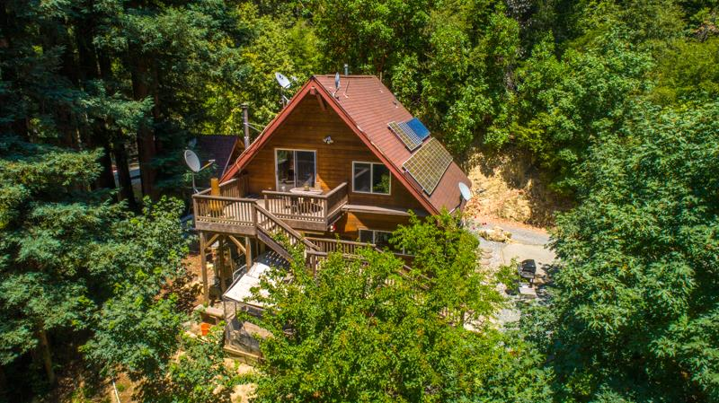 Private off-grid family retreat. Yes, OFF-GRID. No PG&E power outages here EVER! A world away yet under 15 minutes to downtown Los Gatos. Two-story main home. Multiple outbuildings including a spa/tiny house getaway, large container workshop, storage buildings, additional containers and more. Family Compound or rental income potential. This well-loved property is anchored by magnificent old growth, watered by the creek and powered by the sun. Hug a huge ancient redwood in a meditative spot by the creek. Plentiful parking with separation of space and room for large gatherings. This delightful compound is a lovely and special find. Shared gated entry. Partially paved/partially dirt road. Paved driveway to main house.