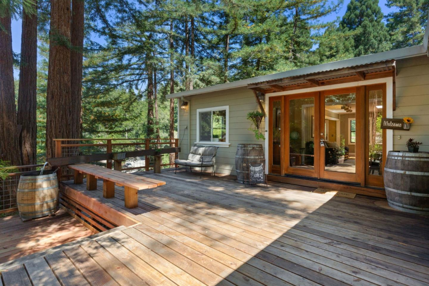 Contemporary single level home in the coveted Forest Lakes neighborhood. Home has 3 bedrooms, 3 bathrooms, plus a study/office, over 2,000 sqft on a sunny .43 acre parcel. The open floor plan is perfect for entertaining! The kitchen has a large island providing plenty of space for cooking and dining. The living room area includes a wood stove fireplace and plenty of natural light from the skylight and windows. The large romantic master bedroom has a wood stove fireplace, bay windows looking out at the beautiful redwoods, and an en-suite master bath with a walk in shower and access to a private bamboo covered patio. The front and back decks are surrounded by redwoods, several of which support a spacious treehouse! Other amenities include 2 car carport, detached garage/workshop, and a large basement storage area. The Forest Lakes community offers a seasonal community pool and activities. Close to shopping & dining in town, Henry Cowell State Park hiking, and easy freeway access.