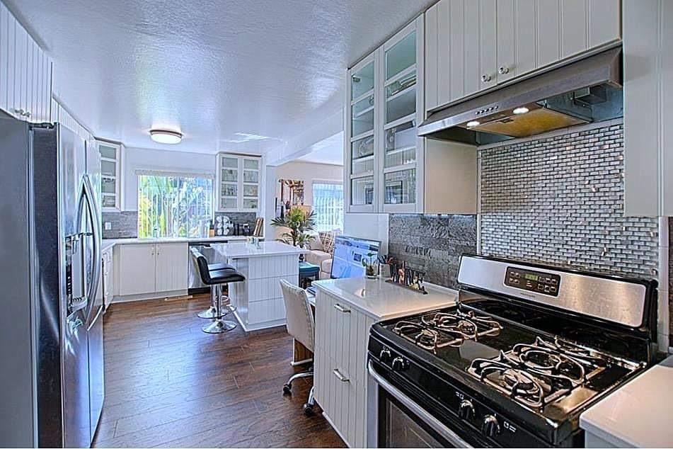Sparkling Jewel in the Capitola Jewel Box. This home has been tastefully remodeled and is ready for fun beach living and entertaining. Beautiful kitchen with stone counters, newer appliances and wine refrigerator. Wonderful island which seats 4-6 and has storage and large counter top. Contemporary style floors and light fixtures throughout. Optional conversion of dining room to a third bedroom which Seller will complete if Buyer wishes. Private patio deck area and outdoor kitchen with BBQ sink refrigerator and kegerator. Pavers, wood deck and seating for 9-10 people at lounge table with gas fireplace. Ensuite bedroom plus a guest bedroom and newly remodeled bathroom. with tile floor and porcelain and glass tile shower,  Great light and sun exposure and well located near beach, Capitola village and shopping. Walk everywhere, get out of your car and explore. Highly desirable neighborhood near park and health spa and organic markets. See video.