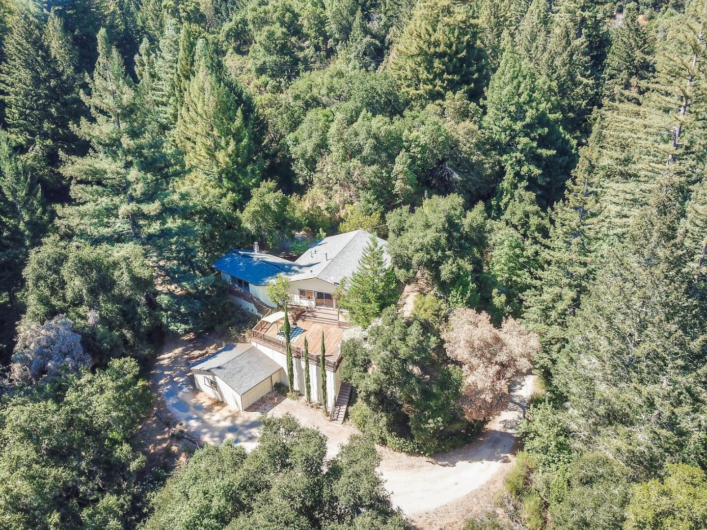 If you are looking for a private, serene getaway in the Santa Cruz mountains with land and an easy living, single level home, you have found it!  Located on 5.75 acres, this property offers beautiful mountain views for those looking to get away from it all.   The one story home is very spacious and features a large living room and separate family room, both with fireplaces.  I love the vaulted ceilings in the living room and the slider and large windows overlooking the expansive deck and views of the mountains.  You have plenty of space for parking larger vehicles and a detached 2 car garage.  Central heat and Air Conditioning.  This home is in the Scotts Valley School District and in a good location for Silicon Valley commuters.  Welcome Home!
