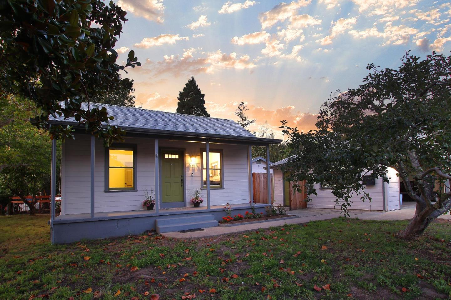 Walk through your front yard to a covered porch entry, inviting you in to this two bedroom one bathroom remodeled space. The main room features a fireplace with stylish built-ins along the wall. The bedrooms are filled with light, with 2 windows in front, and 3 windows in the back which wrap around the corner of the home. The dining area flows to a private patio and the original house then opens to a ground level back bonus studio/living quarters. This area comes ready for your flexible needs. It is perfect for an aging relative, or as an enormous master bedroom if the two front rooms were wanted for different uses.  It is a game room, a rec room, a studio. The area has three sets of double doors that open to enclosed outdoor gardens. It includes a bedroom with built-in closets and a partially equipped elderly accessible bathroom. The garden is an orchard and a gardener's delight. The back planter beds are currently thriving with an abundance of tomatoes. Feel free to take one.