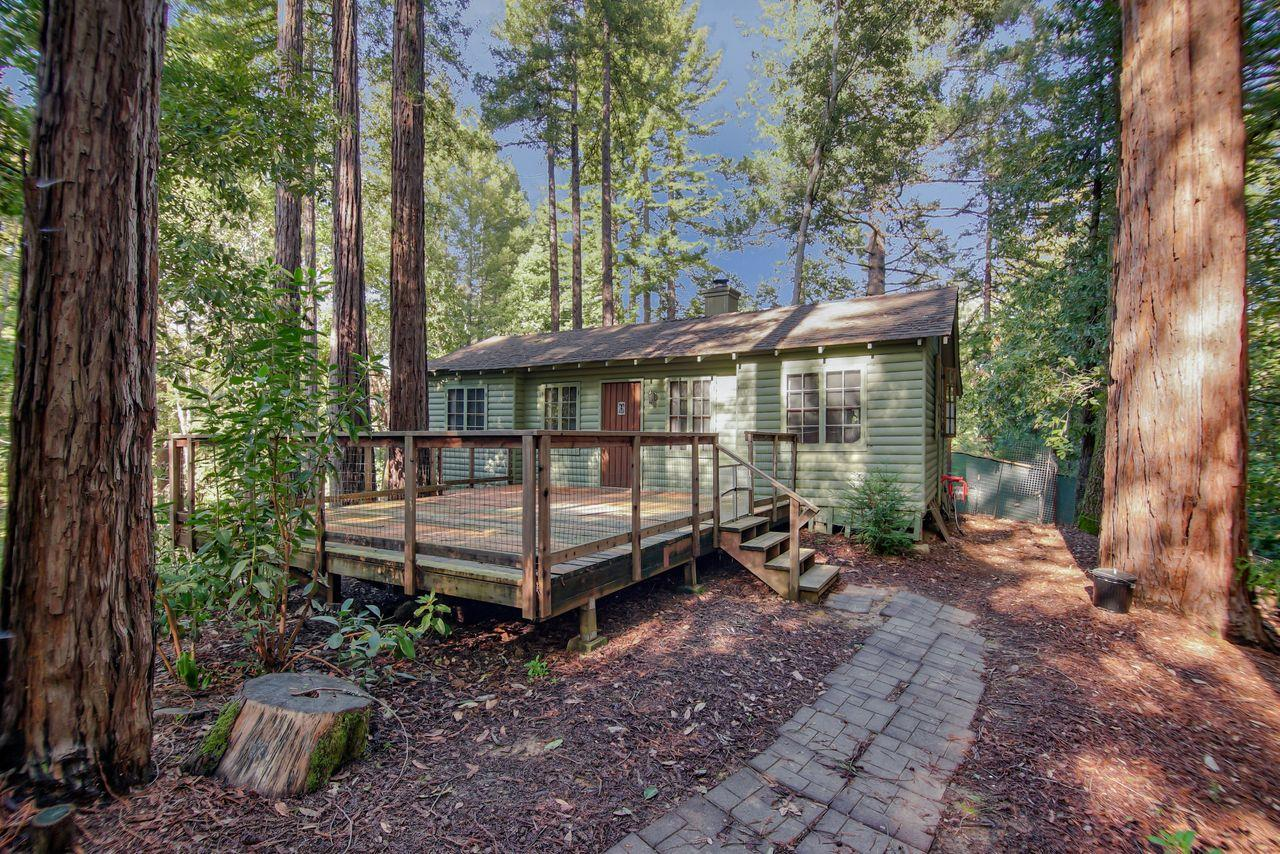 Desirable sunnier location of Forest Lakes. Cabin just 5 minutes from downtown Felton and 15 minutes to Santa Cruz. Two bedroom one bath, end of the road privacy yet one block walk to the park. Parking at street level for one car, walk up 20+ steps to home. Elevated above street level gives a feeling of privacy with sun dappled forest views. Original 1930's Cabin charm and move in ready. Large fenced front deck and nice sized back deck as well. Interior laundry and work/storage area and level carport storage area in the yard.