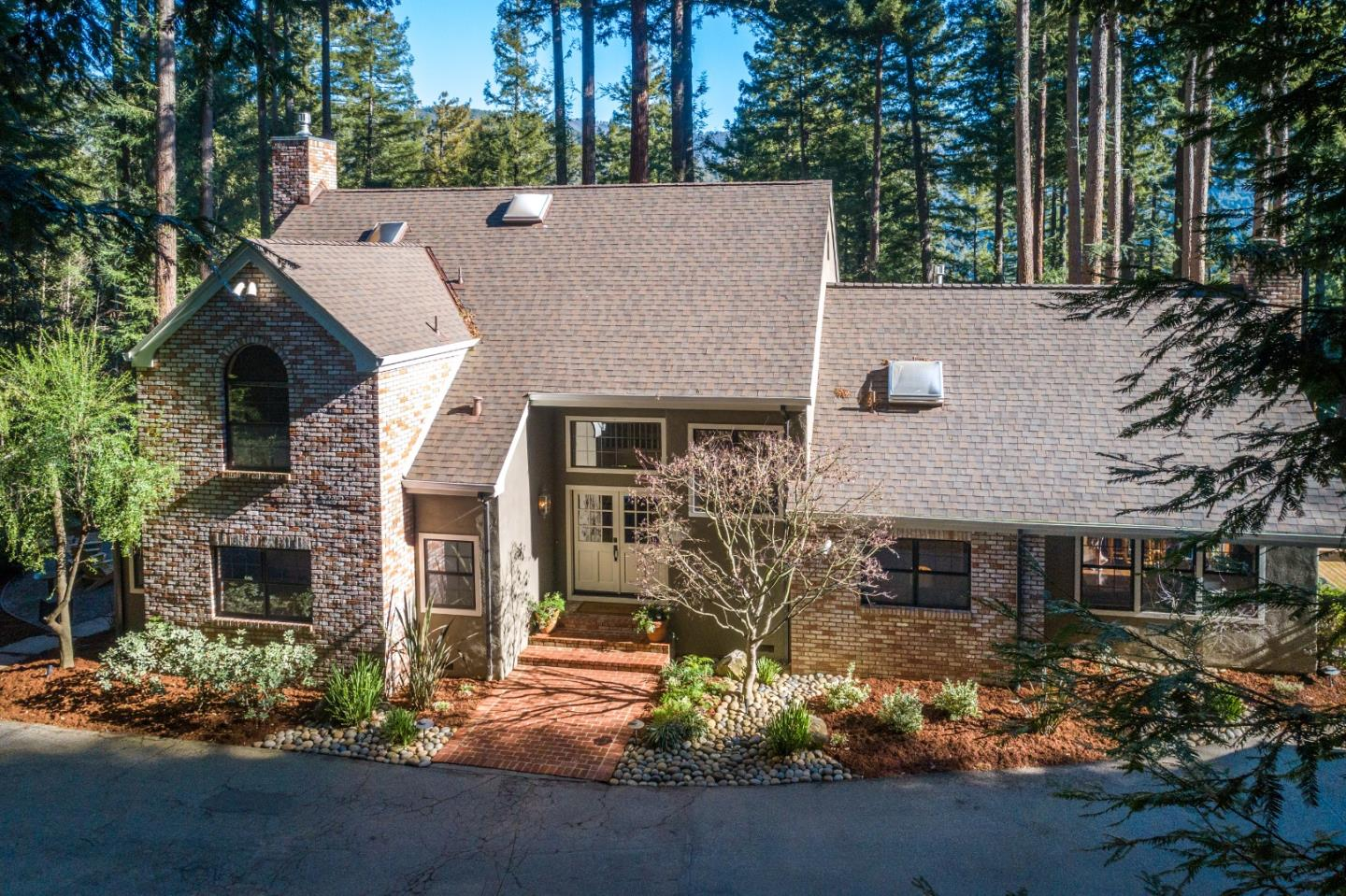Exceptional quality and design enjoying stunning natural surroundings. Beautiful wide plank hickory hardwood floors, travertine stone entry, wool carpeting. Formal dining with built-in hutch & wine refrig. Kitchen & breakfast nook, custom cabinetry, granite counter tops, Thermador appliances. Living room features custom gas stone fireplace, sliding door to patio. Family room w/high ceilings, brick fireplace & wet bar, opens to expansive deck & landscaped backyard. Office, powder room & spacious guest suite also on ground flr. Upstairs 3 spacious bedrooms incl. a lovely master suite, 2 full baths, walk-in attic. The gorgeous backyard is ideal for entertaining. From the hot tub enjoy amazing views of mountains, redwoods and the big starry night sky. Flagstone pathways lead to scenic sitting areas, a large lawn, raised garden beds, treehouse, play structure, sports court. Located in the desirable Summit area close to the store, wineries, Loma Prieta/CT English schls. Easy access to Hwy 17