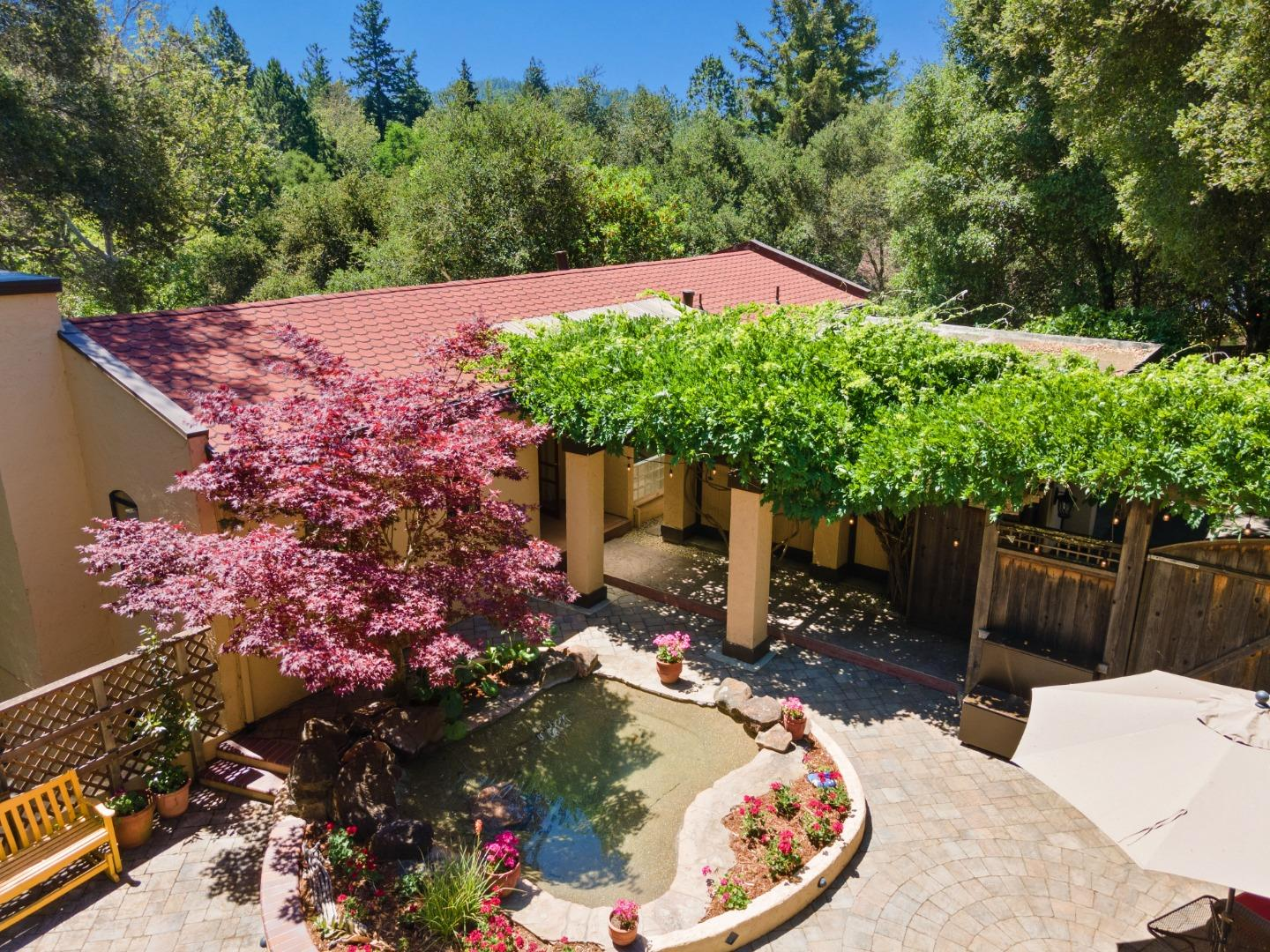 Picturesque, Mediterranean styled home is the perfect modern mountain getaway. Arbored entrance & sparkling pond offer a most spectacular welcome. Arched doorway & formal entry leads to the main living areas, where you are greeted by warm colored walls, tile floors, & whitewashed vaulted ceilings. Numerous skylights & picture windows bring in the natural light. Oversized living room w/ a wood burning fireplace. Kitchen & dining areas are an entertainer's dream featuring gorgeous wood cabinets, stainless steel appliances, ample counter space, and sliders to the deck. All 3 bedrooms are downstairs, the master on one end and the 2 BRs and BA on the other end. Master suite has a walk closet, en-suite bathroom, and sliding doors to a sunny patio & private hot tub. Don't miss the additional detached guest room. Plenty of storage space, including pantry, mudroom, and exterior storage shed. Parcel also offers private creek access, a great mix of sun and shade, and parking for up to 10 cars.