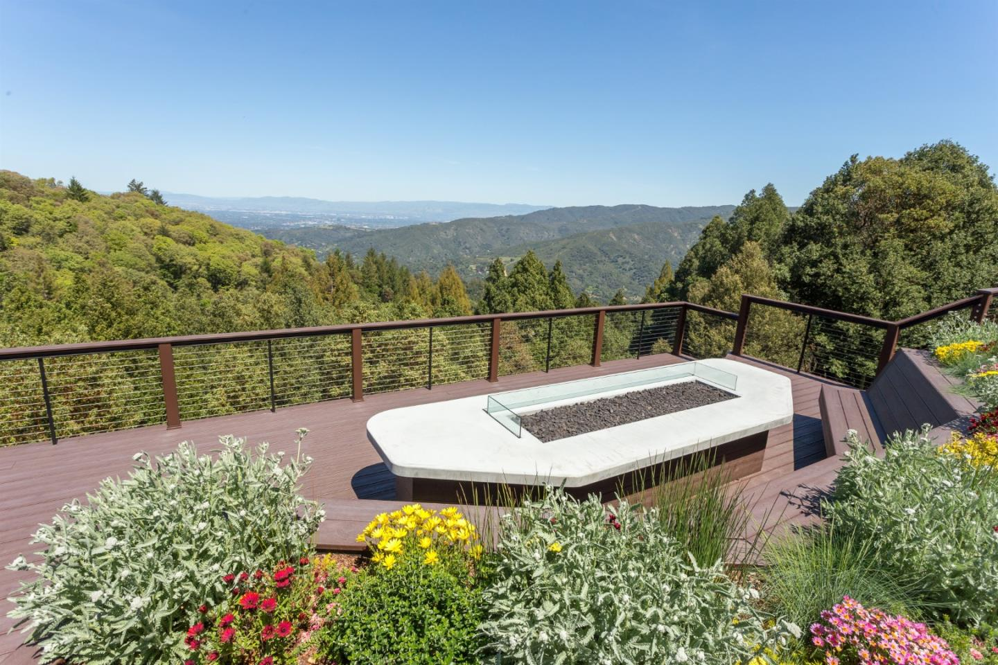 Rare opportunity for a peaceful mountain retreat with close-in location, panoramic views of Los Gatos hills & Silicon Valley! Set back from Summit Rd via a gated circular driveway, on a private knoll top, approx 7.5 acres with bocce ball court, fenced gardens, dry stone walls with stone benches, meandering pathways. Expansive deck with 20' custom gas fire-pit/table, benches, outdoor kitchen, outdoor shower, hot tub & endless pool swim spa. City light views at night. New 4 car garage with 1 bedroom apartment over, approx 780 sq ft with vaulted ceilings, full kitchen, bathroom, laundry, private deck. Main home living room features vaulted ceilings, walls of windows, modern wood panel walls, new wood burning stove and stone surround. Office area with built-in desks/storage, remodeled kitchen, impressive formal dining with prow window. Elevator to lower level media room with full bath, wine cellar, laundry room. Convenient location near 17/Summit, minutes to downtown LG. Los Gatos Schools!