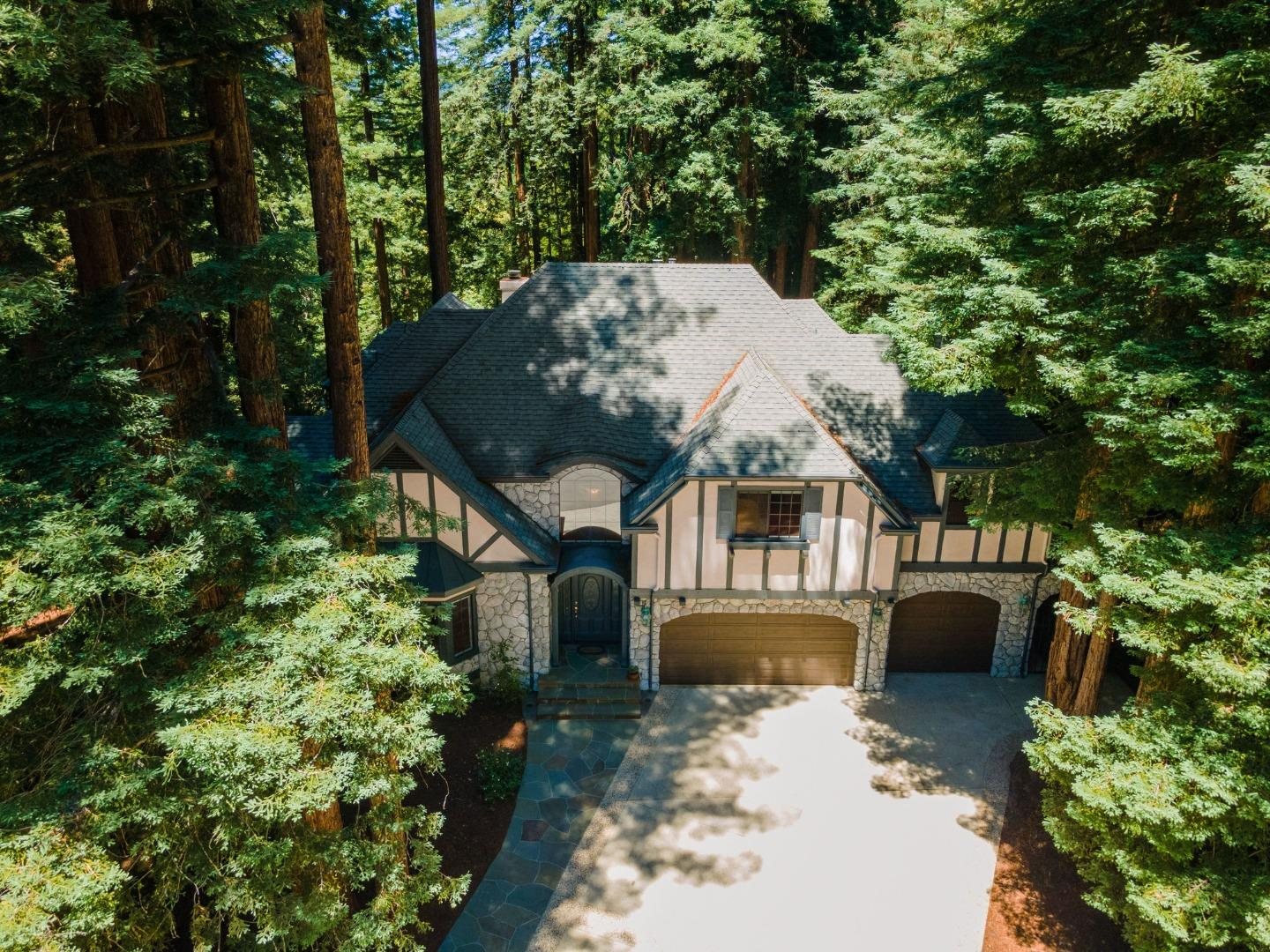 This traditional 4-BR, 4.5 BA Country English-style home is surrounded by redwoods & crafted w/high-quality materials & architectural touches throughout, such as hardwood floors, high ceilings, crown molding, skylights, & custom tile work. The spacious LR is anchored by a dramatic fireplace w/custom carved wood mantel & marble hearth. The huge, custom kitchen has plenty of storage, ample room for the family to gather, & an angled island that adds counter space, bar seating, & an extra sink. A formal dining room w/an arched alcove is adjacent to the kitchen. The main level includes a carpeted master suite w/two master baths, corner office, half bath, & laundry room. A graceful wood staircase curves toward the second story, to three more distinctive bedrooms, bonus room, interspersed w/two bathrooms. Spacious enough for a large family to live w/comfort & privacy, near great schools & Scotts Valleys shops & restaurants, this beautiful home is ready to host a lifetime of happy memories.