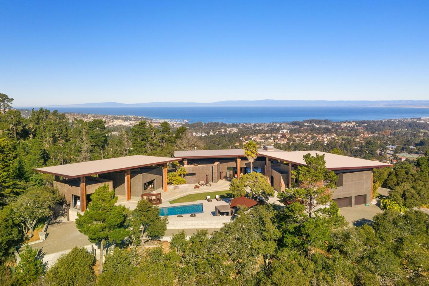 This architecturally stunning modern Ron Mann masterpiece is perfectly placed high on Gentry Hill. The 5-acre property, sitting in the sunshine, takes in panoramic views of the entire Monterey Bay across to Santa Cruz, as well the lush forest horizon of Jacks Peak. The living areas are filled with exquisite finishes and details of skilled artisans. It's your own private luxury wellness resort and spa. Three giant rectangular corten steel roofs appear to float above the concrete buildings, resting on the solid 26 ft tall old growth Douglas Fir columns. The volume of the 18 ft ceilings is magnified by 12 ft glass panels that disappear into the walls, designed for an incomparable indoor/outdoor lifestyle. Every building opens onto the 1/2 acre courtyard; the perfect locale for enjoying the coastal environment and fresh air. A unique estate that is just minutes to all of the recreation and amenities of Carmel, Pebble Beach and the Monterey Peninsula.