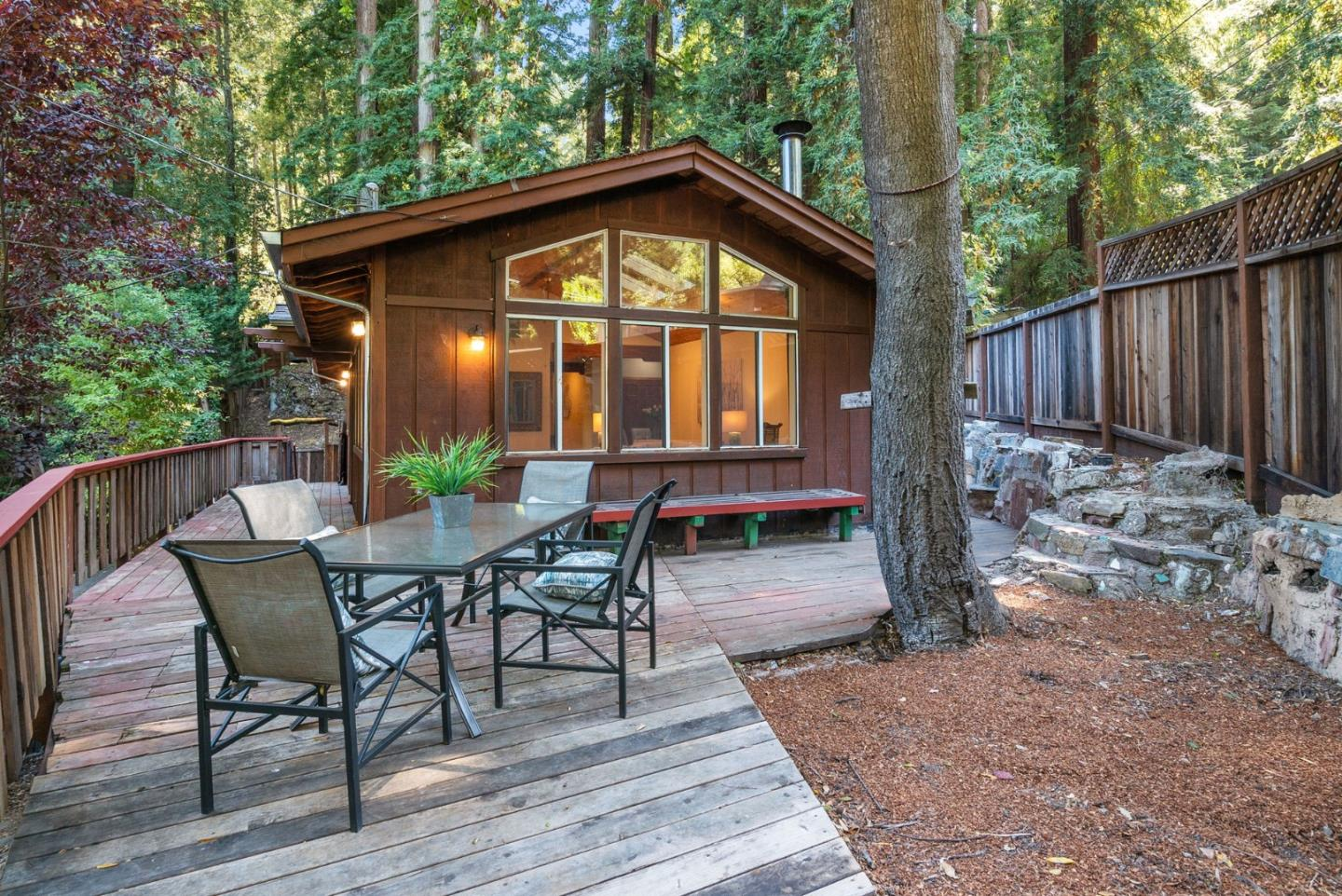 Built into a Felton hillside & ringed by maples, pines, & redwoods, this cozy home feels like a modern treehouse. The living room has a wood stove & a wall of custom windows leading up to an angled pine plank ceiling w/a ceiling fan, skylights, & recessed lights. Wood floors lead to a kitchen/dining area, w/wood cabinets, a gas range, double sink, recessed lights, & more views of the trees outside. The spacious master bedroom has a modern feel & repeats the living room features. A second bedroom or office also has hardwood floors, an angled ceiling, & recessed lights. Between the bedrooms is a bath w/a shower, wood cabinets, & recessed lights. A wooden deck wraps around the house, w/built-in benches & plenty of room for outdoor dining, entertaining, & relaxing. The trees provide both color & privacy, & a small shed offers extra storage space. Cozy & inviting, w/modern touches that add a feeling of space & light, this updated treehouse weaves modern upgrades into a forested retreat.