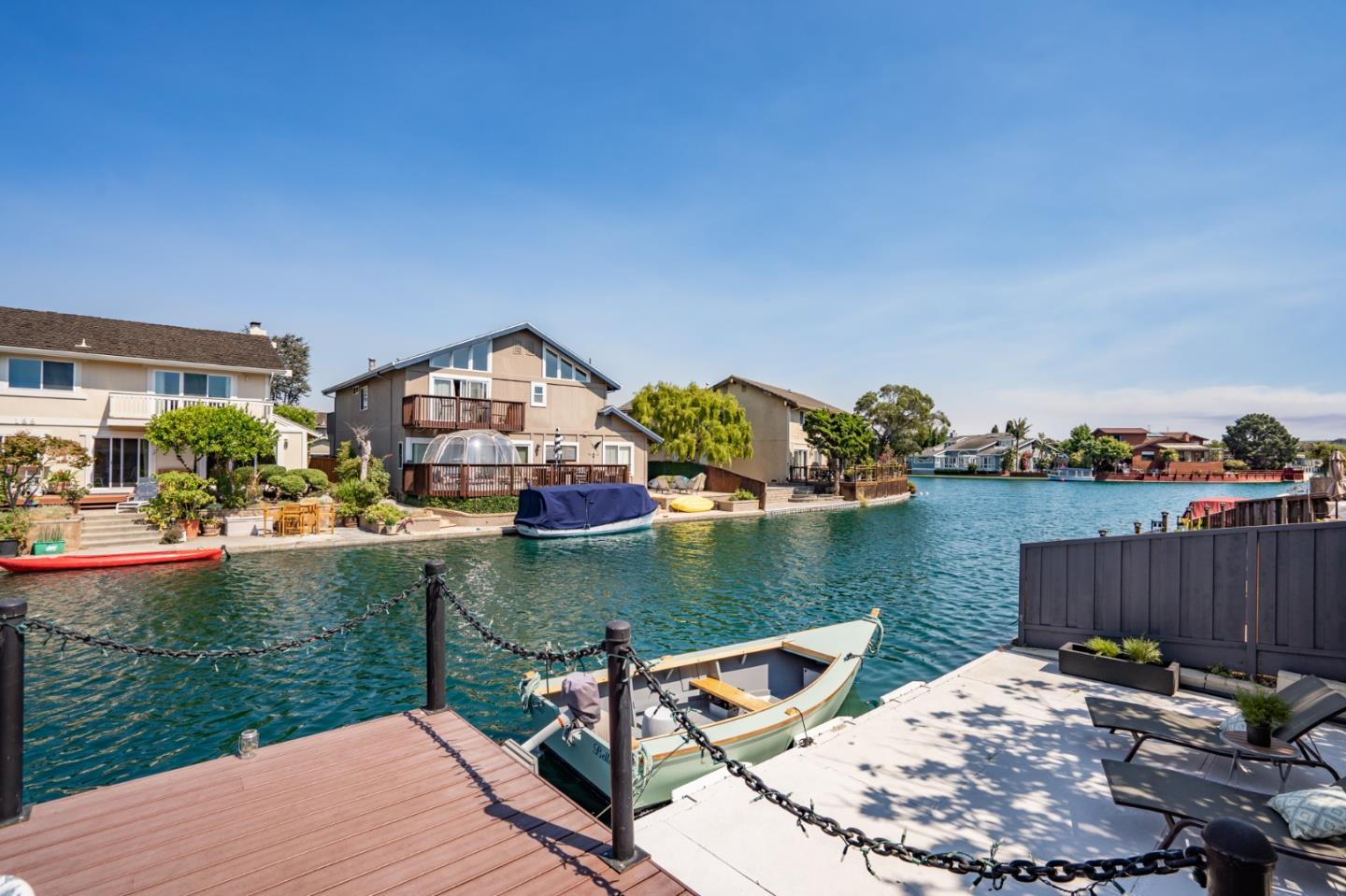 This waterfront home has a spacious single level floor plan. Large windows & fantastic water views & boat deck w/ boat. French doors open to the back yard & patio for a flowing floor plan. The open living, family & dining rooms create an organic space for entertaining, along w/ the stunning chefs kitchen remodeled to today`s standards, including high-end appliances, contemporary custom cabinets & an over sized quartz island. Hardwood floors in all four bedrooms & 2.5 baths have been updated with a modern flair. The generously sized primary bedroom suite features water views & access to the rear deck, 2 separate wardrobe closets, Hunter Douglas blinds w/ black out shades, & a luxurious en-suite bath with over sized walk-in shower, 2 piece rain shower head, Ferrari red soaking tub, heated tile floors, dual sinks & LED Mirrors.  The backyard features a modern paver patio, beautiful mature magnolia tree, artificial turf, cactus garden, along w/a fabulous Trex deck & concrete boat deck.