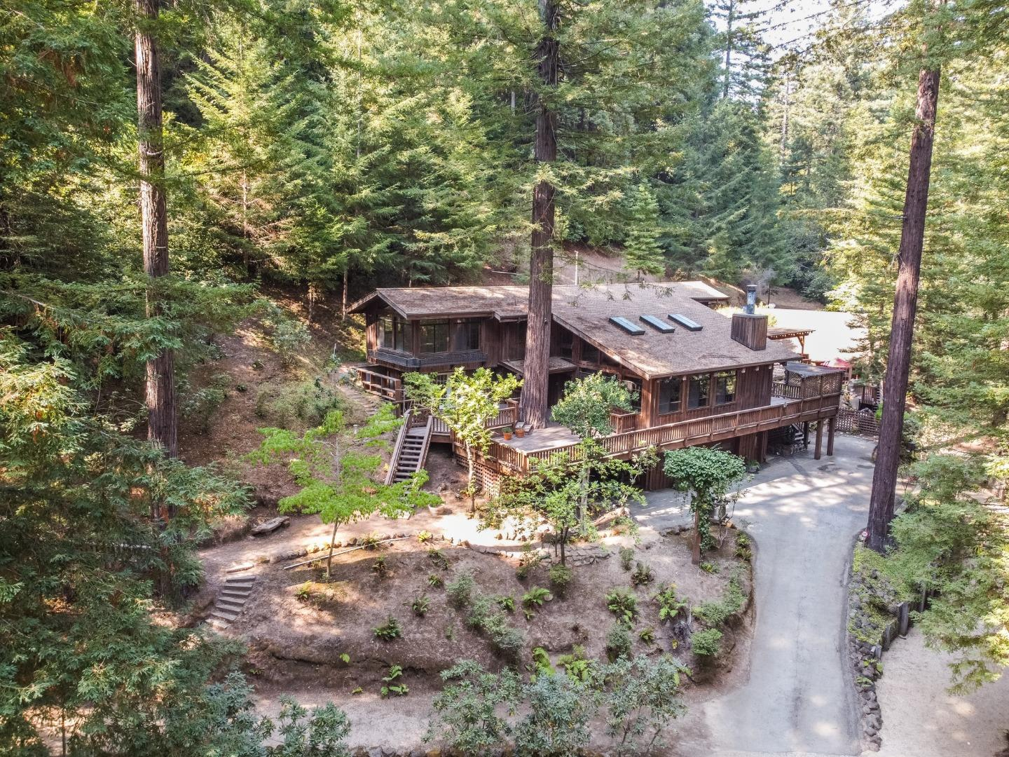 """Once in a lifetime opportunity to own 200+ acres in the Santa Cruz Mountains. After serving in WWII, Don and his sweetheart, Anne, relished their free time hiking in the Santa Cruz Mountains. In 1953, with 3 growing boys, they purchased a large parcel on Love Creek with the dream of creating a family retreat. For decades, the """"Cabin,"""" as family affectionately called it, became a hub for gatherings, campouts, weddings, & celebrations. Before cellphones & WiFi, time was spent swimming in the pond, fishing for trout & wandering miles of trails until Anne rang the dinner bell. The Cabin evolved over the years becoming a larger version of itself to accommodate the growing number of grandchildren & great grandchildren. The main residence & caretaker cottage sit on meticulously maintained grounds. Multiple parcels, each with unique building sites & expansive views, traverse both sides of Love Creek Rd. This Legacy Property is ready for its next owner to create their own lifetime of memories."""