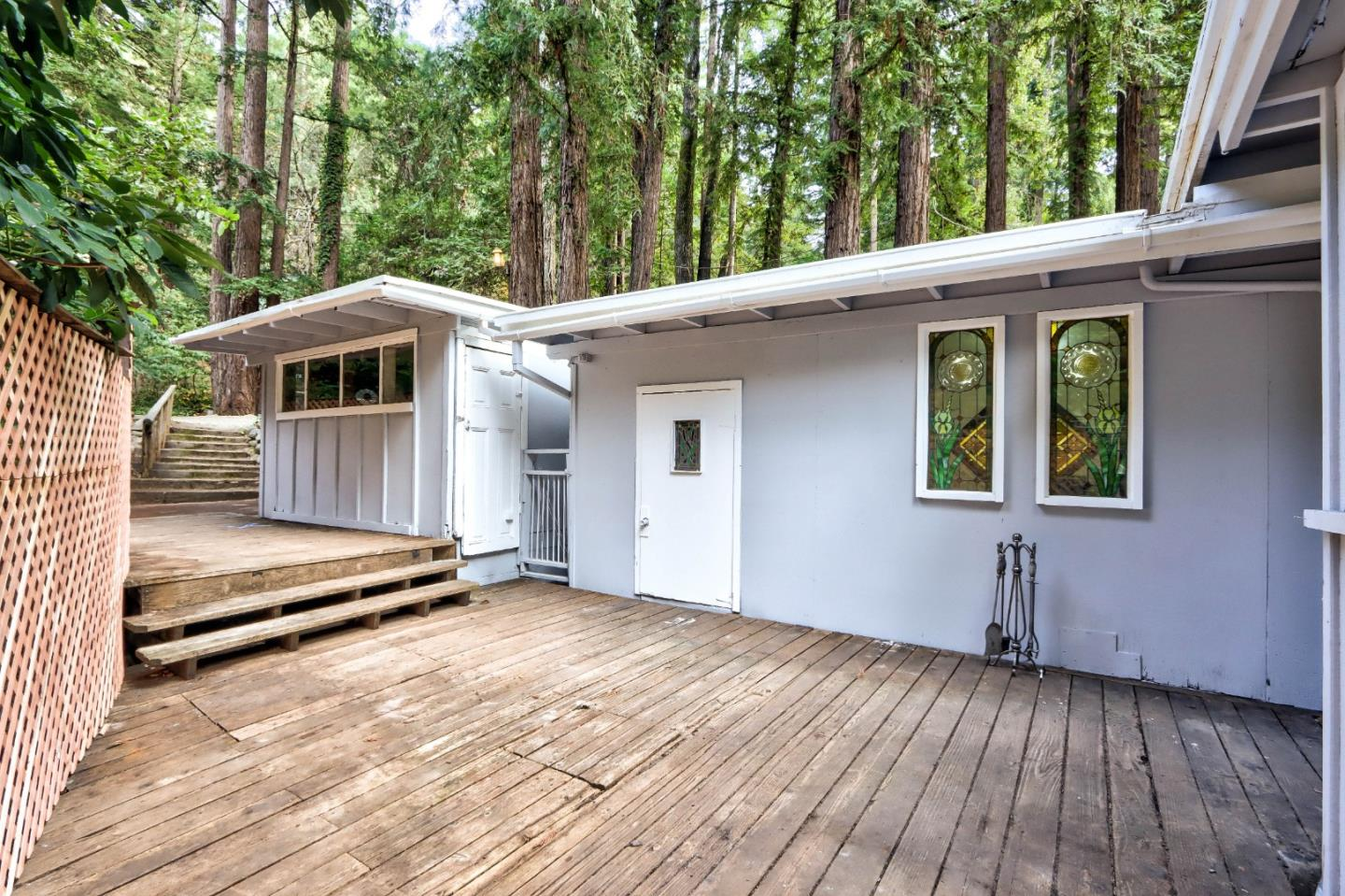 Exquisite Lompico Retreat Full of Character & Charm. Custom stained glass windows in every room fill the home w/ light & beauty, artistic details that you wont find anywhere else. This lovely home features 2 BD/1BA & 2 large workshops. Upper lot is completely flat & usable, almost ½ acre of immaculate forest surrounding the home. Inside fresh carpet, paint & recently installed linoleum flooring create a fresh start for the new owner. Large kitchen is open, w/ a separate dining area & a secret pantry accessed by grabbing a book on a shelf. Living room centers around a cozy wood burning stove & a sunroom fills the space w/ light. Main bedroom w/ direct access to bathroom, has water closet w/ a custom entrance ensuring privacy. Laundry room provides extra storage space. Just 10 minutes to downtown Felton, 25 minutes to Santa Cruz Beaches & 40 minutes over the hill to Apple, Google, Facebook & more! Don't miss this one of a kind opportunity, you have never seen anything like this home.