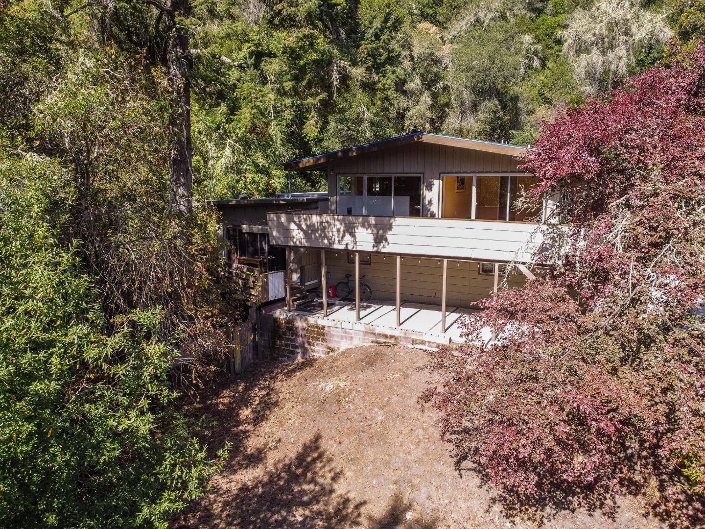 Escape to this peaceful home on over 9 sunny acres yet close to Santa Cruz and Hwy 17. Enjoy south east exposure with your morning coffee on the wraparound deck looking over the mature fir and oak trees. The main house has high ceilings with ample natural light, a large living area with fireplace, kitchen, and 4 bedrooms and 2 bathrooms down the hall. Downstairs is a large basement storage area with a second wash/dryer hook up. Plenty of sunny areas to garden and enjoy nature plus many acres for exploration and privacy. Agricultural zoning allows for many uses. Includes a paved driveway, carport and extra parking area. Minutes from DeLaveaga Park and downtown. Happy Valley schools!