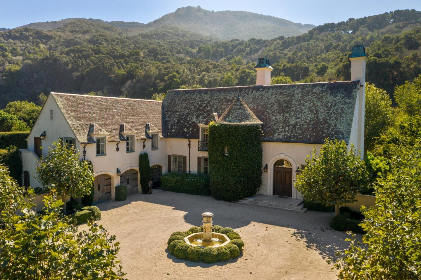 Stunning private estate on nearly 9 secluded acres that front the picturesque Carmel River. The beautiful French chateau is set behind a 15-foot gated entry ensuring maximum privacy.   The 4-bedroom home offers a dramatic great room with vaulted ceilings soaring two stories high, and is filled with beautiful light all day.  The home's living areas embrace the natural surroundings by means of French doors throughout that open out onto stone terraces and patios that seamlessly lead to the expansive and lush landscaped grounds and down to the banks of the River where one can explore nature for hours.  Relax by the serene pool, perfectly set in the verdant grass lawn, it's truly a majestic setting.  This extraordinary retreat offers absolute tranquility in an exquisite natural setting unparalleled on the Monterey Peninsula.  Ideal Mid-Valley location and climate, you will enjoy sun all day yet only 10 minutes inland from the beaches, culture and restaurants of Carmel and Monterey Bay.