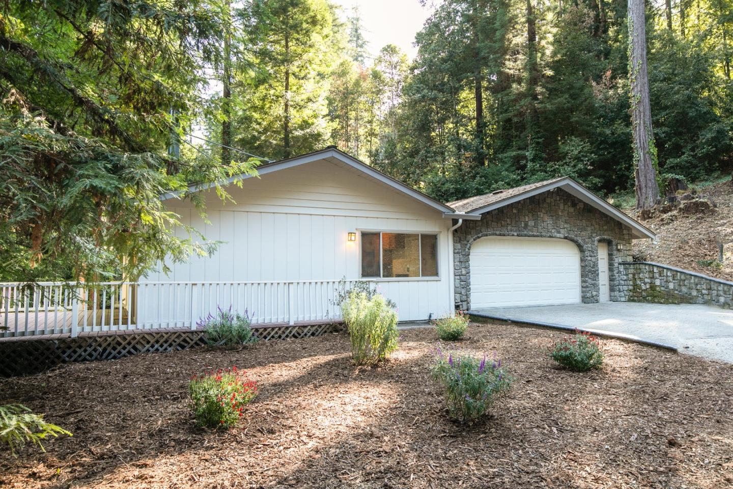 This one-level cottage in the redwoods has an open design. The open-beam, wood, insulated ceilings add a warmth to the spacious great room. The 4 skylights flood the home with natural light. The kitchen was updated in 2008. There is fresh paint inside & outside, brand new LVT flooring plus a brand new stove. This abode is conveniently attached to a 1378sf garage!! This garage is HUGE!! If you need an at home shop or if you have 6 cars that you want inside of your garage or if you collect A LOT of stuff then this is the garage for you! There are FOUR 220 outlets in the garage + plugs all the way down every wall. There is also an attic the length of the garage,  so LOTS of storage space. Just 5 minutes to the conveniences of Ben Lomond, this location benefits from Comcast high-spd internet & San Lorenzo Valley Water. Come see this sweet abode & monster garage before it's gone! Check out the 3D virtual walk thru tour! Agent available to host open by appt Sat/Sun if appts get prescheduled.