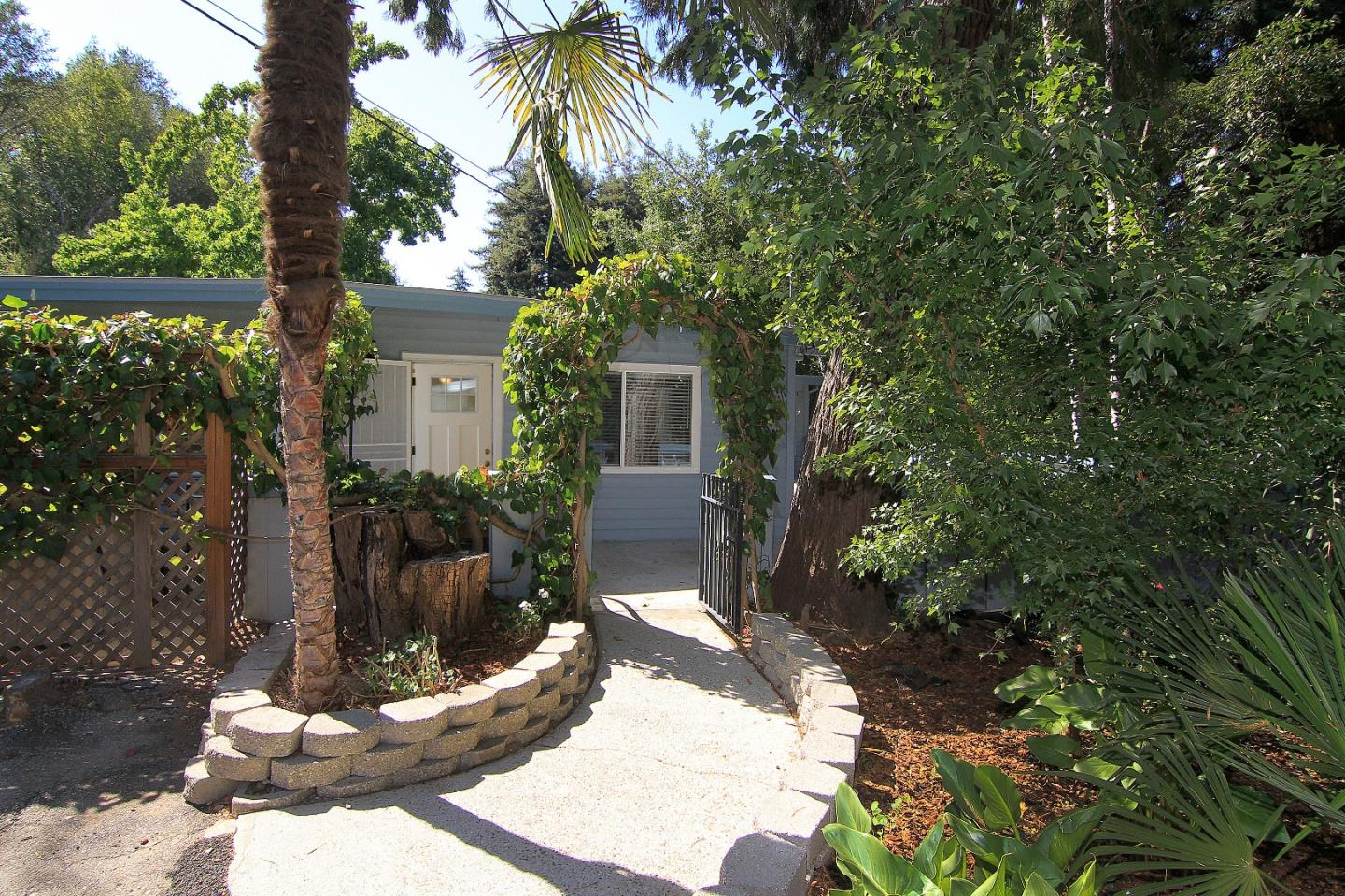 This is a rare find.  Single level home with second unit and a substantial workshop and garage on a 1+ acre lot.  The main home has 4 bedrooms and 2 updated bathrooms with an open floor plan kitchen/living room and adjoining pantry.  French doors open onto a large patio with views of the redwoods and canyon.  Separating the two homes is an enclosed garden area with 2 raised wood planters.  The one bedroom second unit has a new kitchen and updated bathroom with a private deck at the rear.  Both units have been newly painted, have tankless water heaters and new wood style linoleum flooring throughout.  The icing on the cake is a large workshop with a multi car garage.  There are numerous places to park on the property, including two covered parking areas which can accommodate multiple cards and/or recreation vehicle.  This is a unique property offering the bonus of 2 homes plus an expansive workshop.  All square footage quotes are estimates.  Buyer to verify.