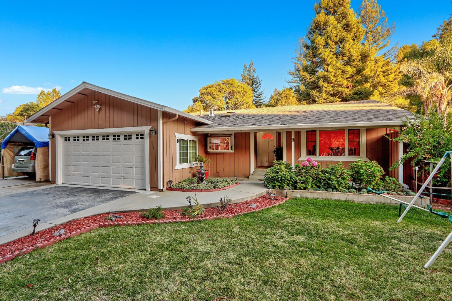 Beautiful home in Scotts Valley, remodeled and move in ready. A flat and Sunny lot has mature fruit trees, a green lawn, large veggie garden and multiple hard-scaped patios. Plenty of parking thanks to the 2 car garage and circle driveway. Enter into a large, well laid out home perfect for entertaining. To the right is a parlor with a built in bar, that leads out onto the back patio. To the left, a warm kitchen welcomes you into the heart of the home. Custom hickory cabinets and granite counters complement the high end stainless steel appliances, including a meile espresso machine. Hardwood floors throughout bring warmth to the living space. Kitchen opens into a spacious dining area. Large living room has cozy fireplace, high ceilings and opens onto second patio. Large main suit retreat has vaulted ceilings w/ exposed wood beams, a cozy sitting area w/ wood stove and an ensuite bathroom. 2 more bedrooms are large and cheerful, with access into the back yard. Great commute location!