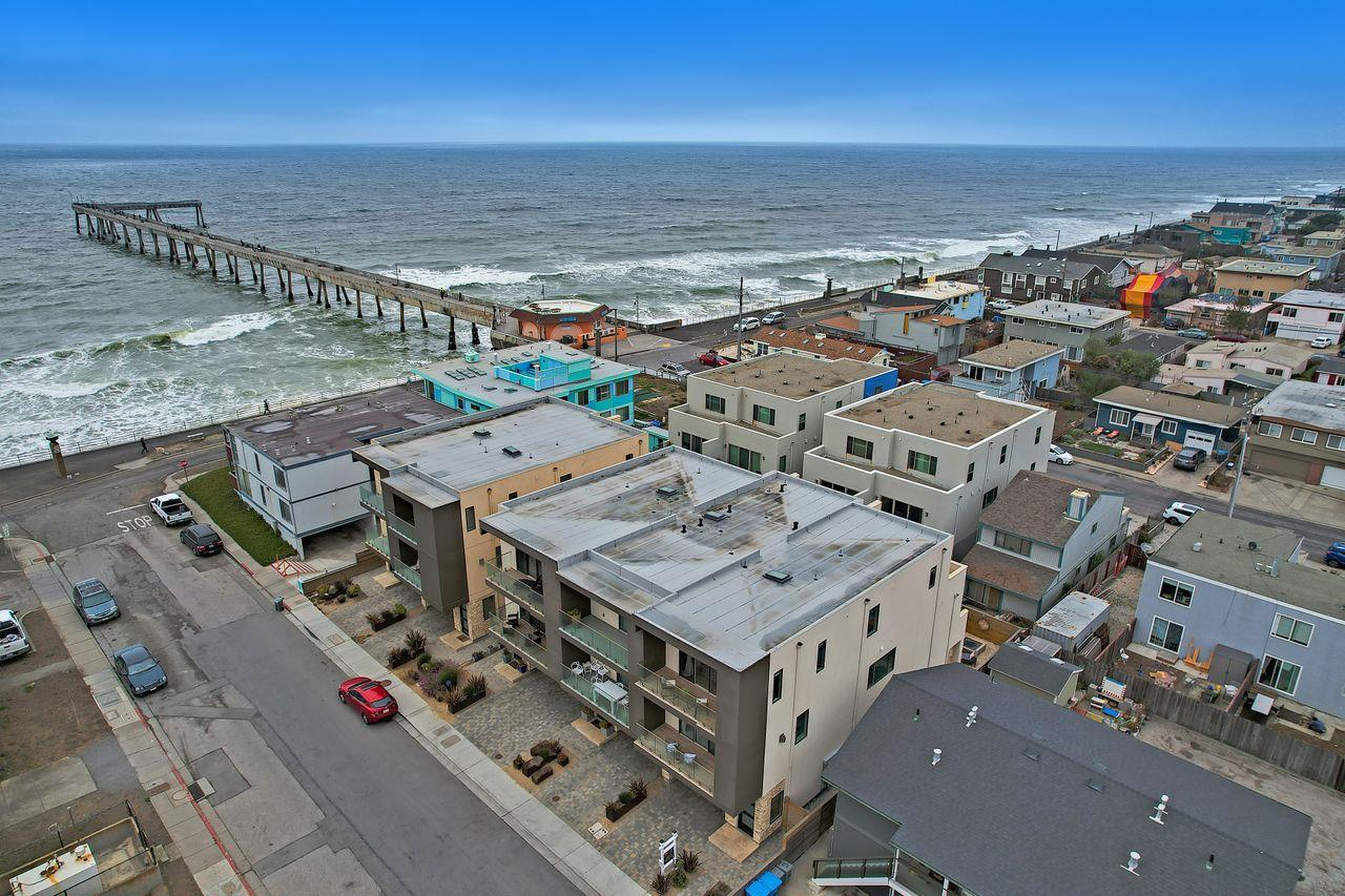 Chic, ocean view condo near the beach, pier, shops and golf course - a dream location, watching the pelicans fly by, listening to the sounds of the surf. Built in 2017, this bright and luxurious end-unit offers 4 bedrooms and 3.5 (en suite) bathrooms with heated floors - and about 2,190 feet of living space. Enjoy this clean, modern style with designer paint and wallpaper, marble, stone and wood flooring, high-end kitchen appliances and many custom finishes. Downstairs and side access to rear yard with raised beds and gas fire pit. Garage is complete with electric car charger, tankless water heater, storage racks, and epoxy floors. Fantastic work from home location, or easy commute to San Francisco and the peninsula. Experience coastside living at its finest!