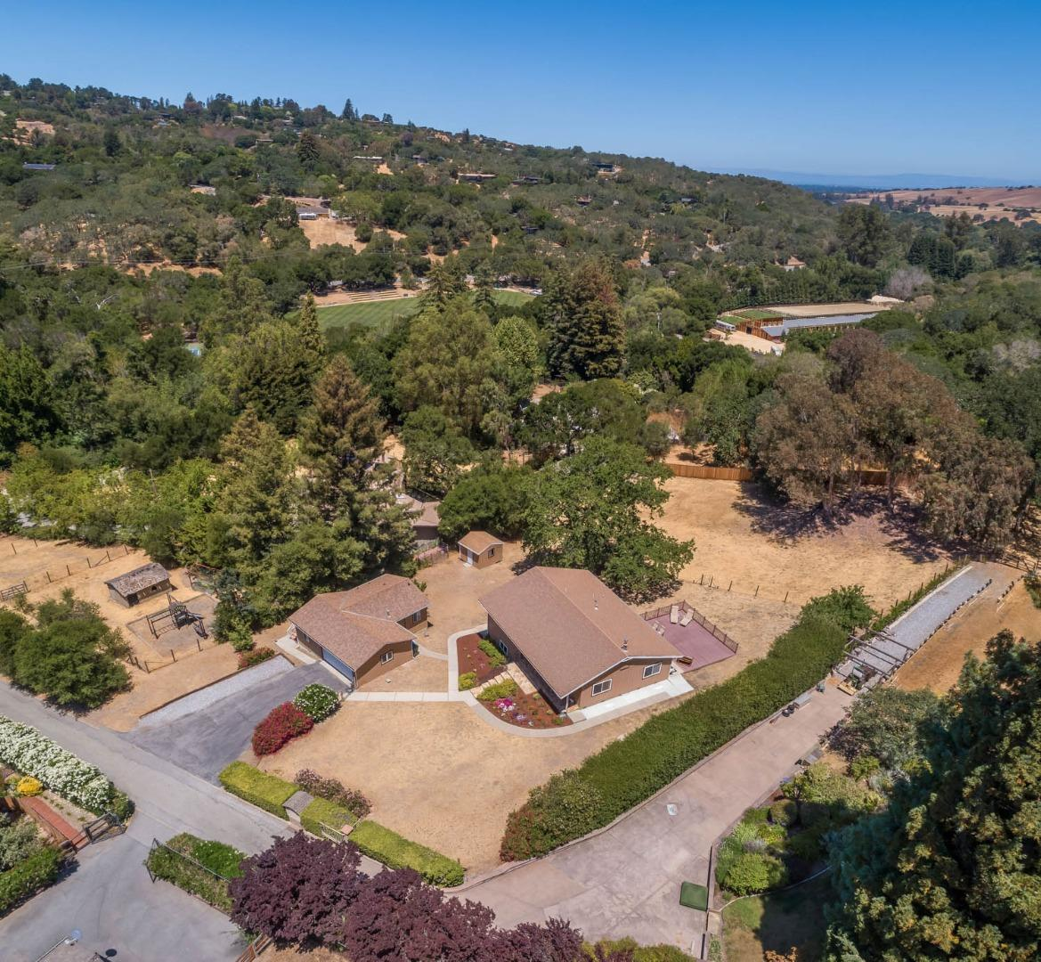 Tucked away on one acre (per county) in desirable Portola Valley, this 2-bedroom, 2-bath home with a guest house/rental unit offers privacy and comfortable living. The mostly level property is fully fenced with views of Windy Hill and an abundance of outdoor space including an area suitable for horses. The main level includes the spacious living room that connects seamlessly to the airy kitchen. A large deck is accessible from the kitchen making the entire space ideal for indoor and outdoor entertaining. A lower level offers two generous-sized rooms with storage and yard access. The detached garage includes a connected guest house that is perfect for use as a rental unit or visiting guests. Built in 1990, the unit is entered from a private deck and includes a living room, kitchen, stacked washer/dryer, and one bedroom with an en-suite bath. This desirable location is convenient to local shopping and restaurants, hiking trails, highway 280, and Stanford University.