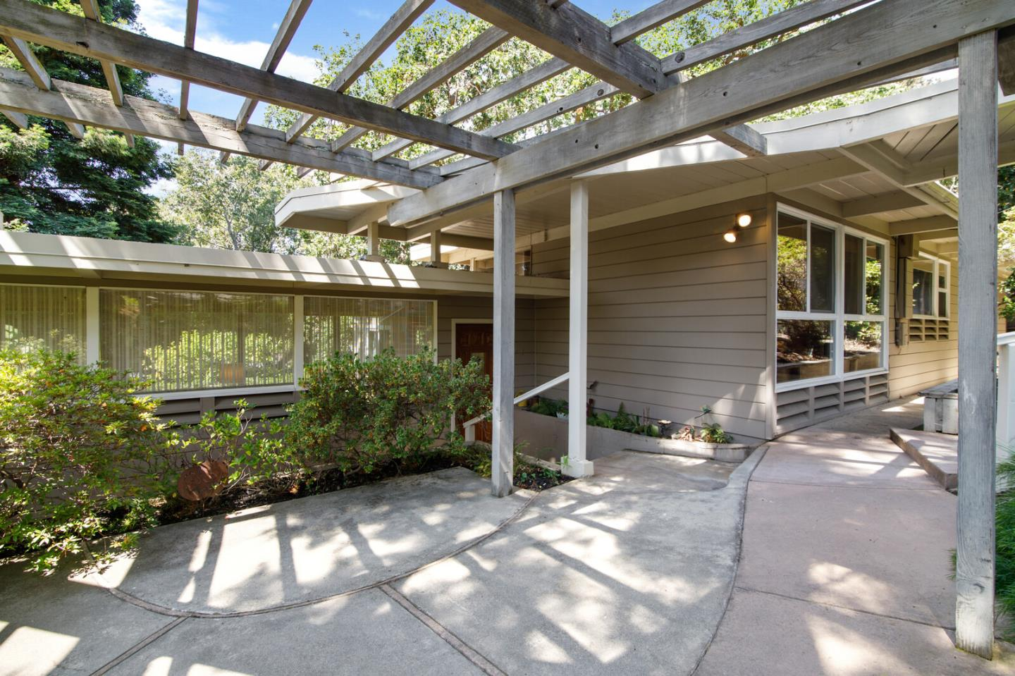 Fall in love w/ this mid-century modern beauty! Stately pines & peaceful patio setting welcome as you enter formal LR w/ FP, while floor to ceiling windows bring nature to your door! Formal DR, counter bar seating & eat-in kitchen make entertaining a breeze. Built in office nook & laundry room lead directly to garden w/ grapefruit & lemon trees, perfect for weekend BBQs, birthday parties & dining al fresco. Relax on the redwood deck w/ built in benches & flat lawn area beneath majestic redwoods & oak tree canopy. Primary BR provides a cozy retreat w/ FP, convenient backyard access, en suite bath and 2 walk-in closets! 2nd bath & 2 additional BRs conveniently located off main hall, each showing nicely w/ double closets & morning sun. Carpets, tile flooring, beamed ceilings & abundant storage throughout, as well as Eichler-like architectural style complete the story in a truly one-of-a-kind home. Walking distance to parks, schools & Downtown San Carlos make for the ideal location!