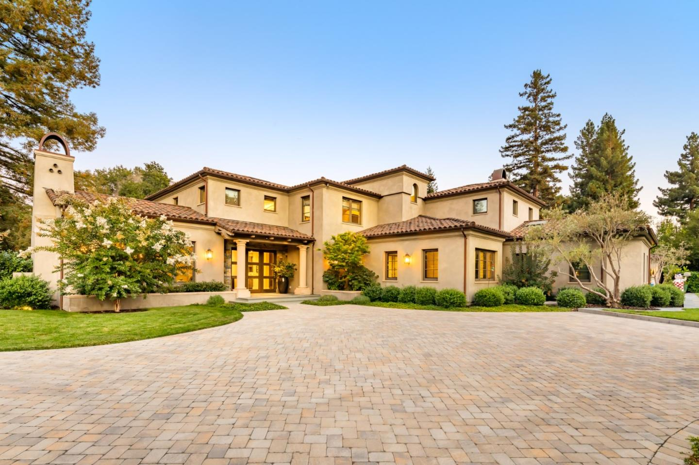 Grounds of over 1 acre provide an intimate setting for this spectacular estate, custom-built in 2017. Natural tones create a warm, welcoming ambiance that puts you at ease, with a quiet elegance that emanates throughout over 9,300 total square feet of interior space. The modern floorplan offers grand-scale formal rooms made for entertaining, plus a kitchen with top-of-the-line appliances, an office, family room, theater, wine cellar, and more. 5 bedrooms and 7 bathrooms include the detached pool house, as well as 4 en suite bedrooms in the main home highlighted by the primary suite with a spa-like bathroom. Numerous glass doors open to grounds filled with heated terraces, a fireplace, grilling station, and a lap pool. Plus, ample parking is always available thanks to a gated motor court and 4-car garage. Just moments to downtown Menlo Park, this estate is also convenient to downtown Palo Alto and Stanford University, with the venture capital firms along Sand Hill Road close at hand.